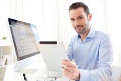 Jeune homme d'affaires travaillant à la maison sur son comprimé photo stock