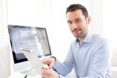 Jeune homme d'affaires travaillant à la maison sur son comprimé images stock