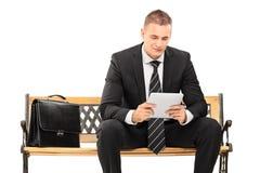 Jeune homme d'affaires travaillant à un comprimé Photographie stock