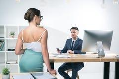 Jeune homme d'affaires travaillant au bureau et regardant la femme d'affaires séduisante se tenant dans le bureau Images stock