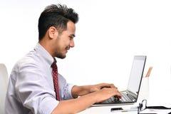 Jeune homme d'affaires travaillant avec l'ordinateur portable photographie stock