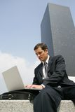 Jeune homme d'affaires travaillant avec l'ordinateur portatif à l'extérieur photo stock