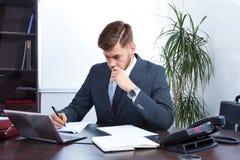 Jeune homme d'affaires travaillant dans le bureau Photos libres de droits