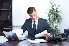 Jeune homme d'affaires travaillant dans le bureau Photographie stock