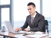 Jeune homme d'affaires travaillant dans le bureau Photographie stock libre de droits