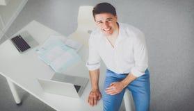Jeune homme d'affaires travaillant dans le bureau, se reposant au bureau photo stock