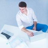 Jeune homme d'affaires travaillant dans le bureau, se reposant au bureau Photographie stock libre de droits