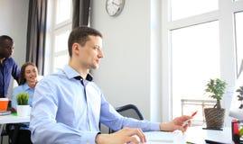 Jeune homme d'affaires travaillant dans le bureau, se reposant au bureau Photos stock