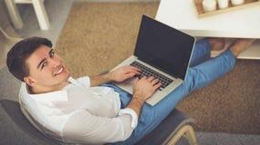 Jeune homme d'affaires travaillant dans le bureau, se reposant au bureau images stock