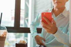 Jeune homme d'affaires travaillant dans un café vérifiant le sien téléphone Image libre de droits