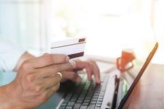 jeune homme d'affaires travaillant sur son ordinateur portable et employant la carte de crédit se reposant à la table en bois dan Photographie stock