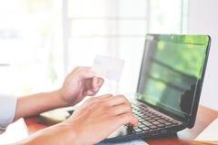 jeune homme d'affaires travaillant sur son ordinateur portable et employant la carte de crédit se reposant à la table en bois dan Image stock