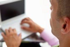 Jeune homme d'affaires utilisant l'ordinateur portatif Photo stock