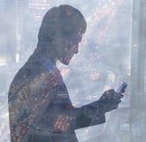 Jeune homme d'affaires utilisant son téléphone portable, double exposition au-dessus de circulation urbaine la nuit, Pékin, Chine Image libre de droits