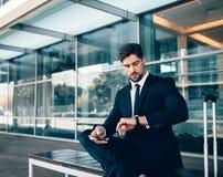 Jeune homme d'affaires vérifiant le temps à l'aéroport Photo libre de droits