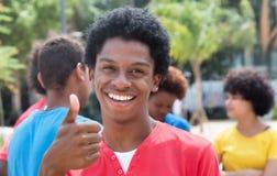 Jeune homme d'afro-américain avec des amis montrant le pouce Photo libre de droits
