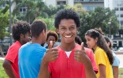 Jeune homme d'afro-américain avec des amis montrant les deux pouces Image stock