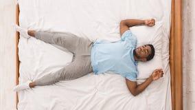Jeune homme d'afro-américain dormant dans la vue supérieure de lit images libres de droits