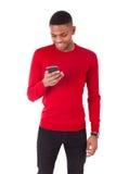 Jeune homme d'afro-américain envoyant un message textuel sur son smartph photo stock