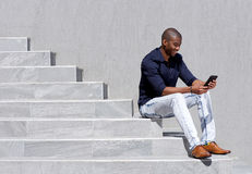 Jeune homme d'afro-américain s'asseyant sur des étapes utilisant le comprimé Images libres de droits