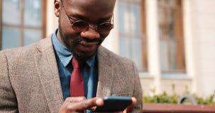 Jeune homme d'Afro-américain s'asseyant sur un banc et dactylographiant à son téléphone intelligent Concepts d'affaires et de mod banque de vidéos