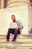 Jeune homme d'Afro-américain travaillant sur l'ordinateur portable dehors dedans Image stock
