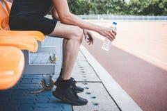 Jeune homme d'athl?te de forme physique se reposant sur le banc avec la bouteille de l'eau pr?parant au fonctionnement sur la voi photographie stock libre de droits