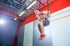 Jeune homme d'exercice de muscle- faisant la séance d'entraînement convenable de croix intense au gymnase sur les anneaux gymnast images stock