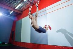 Jeune homme d'exercice de muscle- faisant la séance d'entraînement convenable de croix intense au gymnase sur les anneaux gymnast image libre de droits