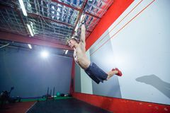 Jeune homme d'exercice de muscle- faisant la séance d'entraînement convenable de croix intense au gymnase sur les anneaux gymnast photographie stock