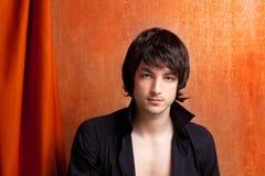 Jeune homme d'indie de bruit de sembler britannique de roche sur l'orange Photos stock