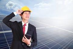 Jeune homme d'ingénieur se tenant dans l'énergie solaire avant sur le Cl de ciel bleu photographie stock