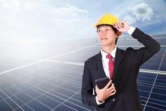 Jeune homme d'ingénieur se tenant dans l'énergie solaire avant sur le Cl de ciel bleu photo libre de droits