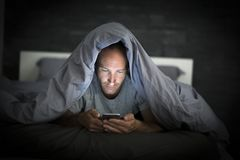 Jeune homme d'intoxiqué de téléphone portable éveillé tard la nuit dans le lit utilisant le smartphone image libre de droits