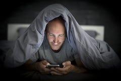 Jeune homme d'intoxiqué de téléphone portable éveillé tard la nuit dans le lit utilisant le smartphone photographie stock