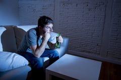 Jeune homme d'intoxiqué de télévision s'asseyant sur le sofa à la maison regardant la TV et buvant la bouteille à bière images libres de droits