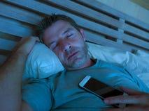 Jeune homme d'intoxiqué d'Internet dormant sur le lit tenant le téléphone portable dans sa main la nuit dans le smartphone et l'a photographie stock libre de droits
