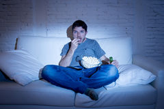 Jeune homme d'intoxiqué de télévision s'asseyant sur le sofa à la maison regardant la TV manger du maïs éclaté et boire la boutei Images stock