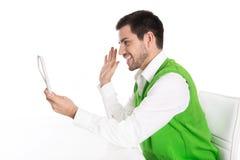 Jeune homme d'isolement d'affaires parlant avec le port de tablette Photographie stock