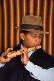 Jeune homme d'Otavalo, Equateur, jouant la cannelure de quena Photos stock