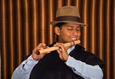 Jeune homme d'Otavalo, Equateur, jouant la cannelure de quena Images stock