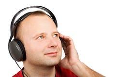 Jeune homme dans des écouteurs Photographie stock libre de droits