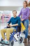 Jeune homme dans des achats de fauteuil roulant avec l'épouse Image stock