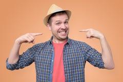 Jeune homme dans des expositions de chapeau d'été sur ses dents images libres de droits