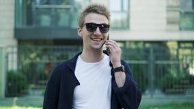 Jeune homme dans des lunettes de soleil parlant sur le téléphone et rire banque de vidéos