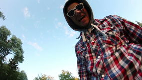 Jeune homme dans des lunettes de soleil posant à l'appareil-photo banque de vidéos