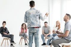 Jeune homme dans l'équipement de denim parlant à un groupe d'adolescents avec Photo libre de droits
