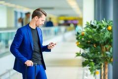 Jeune homme dans l'aéroport avec l'embarquement de attente de bagages Images libres de droits