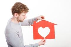 Jeune homme dans l'amour avec la maison de papier Photo stock