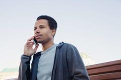 Jeune homme dans l'usage de sport parlant au téléphone portable Type dehors Photos stock